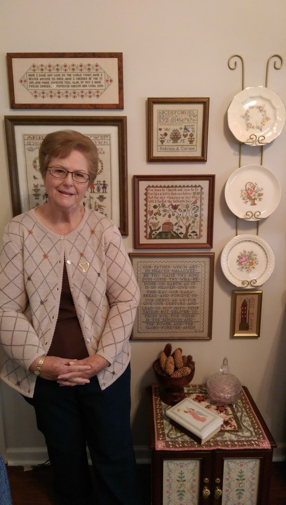 Pat Carson at home in front of her sampler wall